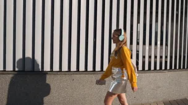 Portrét mladé roztomilé atraktivní mladá dívka v městské pozadí poslechu hudby pomocí sluchátek. Žena nosí žluté halence a stříbrná sukně