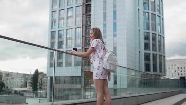 Roztomilý bezstarostné Millenial Hipster dívka s Fun a úsměv, městských ulicích města na pozadí