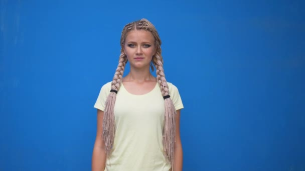 Smiling woman portrait. Young business woman professional looking at camera happy. Beautiful blond female model on blue background with braids pigtails hairstyle