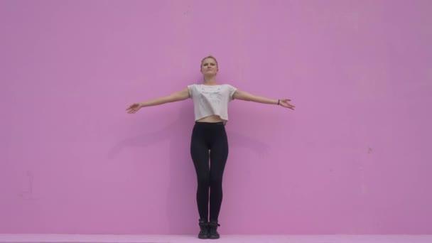 Sportovní mladá žena, která dělá cvičení jógy, které jsou izolovány na růžovém pozadí - koncept zdravého života a přirozenou rovnováhu mezi tělem a duševní vývoj