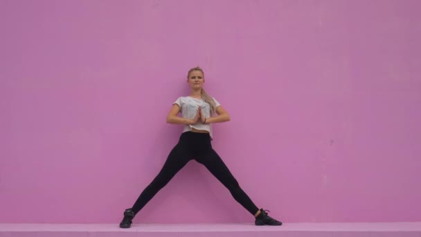 Sporty young woman doing yoga practice isolated on pink background - concept of healthy life and natural balance between body and mental development.