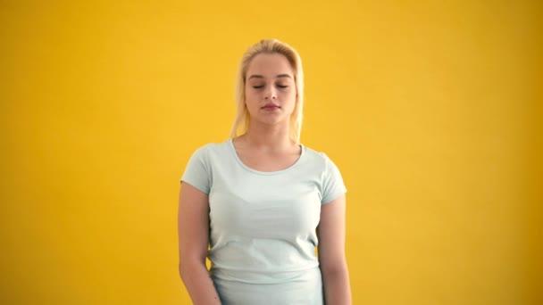 Attraktive junge blonde Kaukasische plus -Size-Model schauen in die Kamera gelben Hintergrund