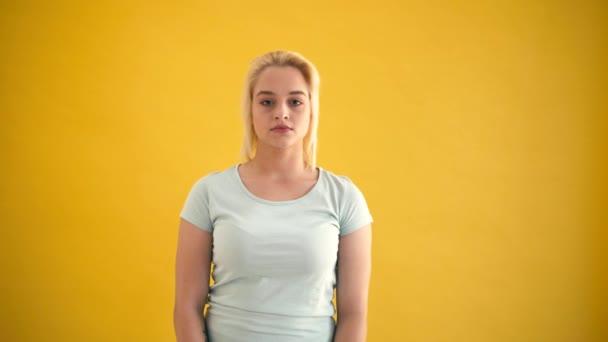 Junge blonde Kaukasische plus Size-Model lustig überrascht auf gelbem Hintergrund-Slow-motion