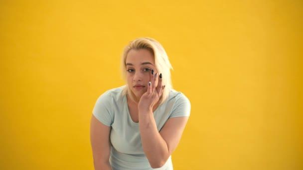 Plus Größe Modell Touch wie ihr Gesicht Make-up und Blick auf Kamera in Spiegel auf gelbem Hintergrund