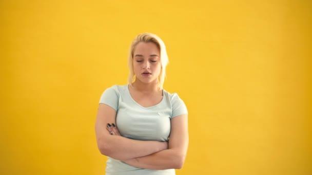 Traurige blonde Kaukasische plus -Size-Model in einer schlechten Stimmung auf gelbem Hintergrund-Slow-motion