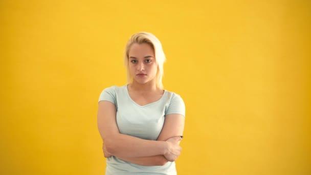 Emotionale blonde Kaukasische plus -Size-Model in schlechte Laune auf gelbem Hintergrund-Slow-motion
