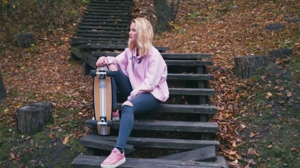 Docela krásné světlé bokovky žena pózuje v lese s skateboard longboard