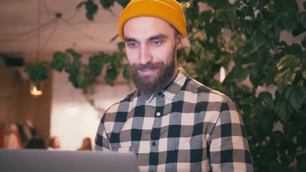 Csípő ember sárga kalapban, hordozható számítógépet használ, és dolgozik, miközben ül a kávézóban, vagy közösségi tér iroda