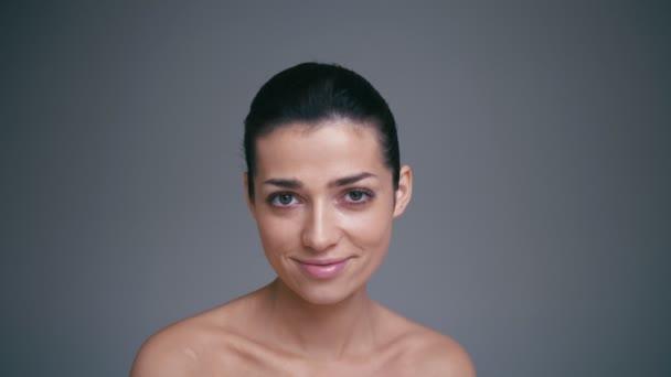 Portrét krásné usměvavé happy bruneta žena s jasnýma očima. Koncept péče o pleť Zpomalený pohyb