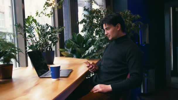 Smíšené rasy muži, kteří pracují s notebookem pomocí chytrého telefonu a pití v café latte