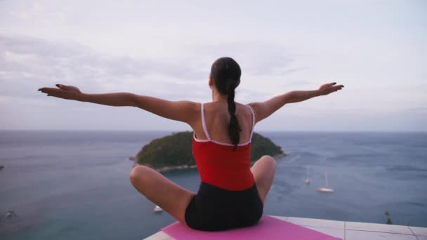 Woman practicing yoga fitness exercise on high place with amazing view of island at sunrise