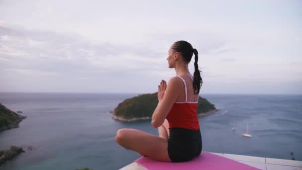 Žena cvičí jógu kondiční cvičení na vyvýšeném místě s úžasným výhledem na ostrov při východu slunce
