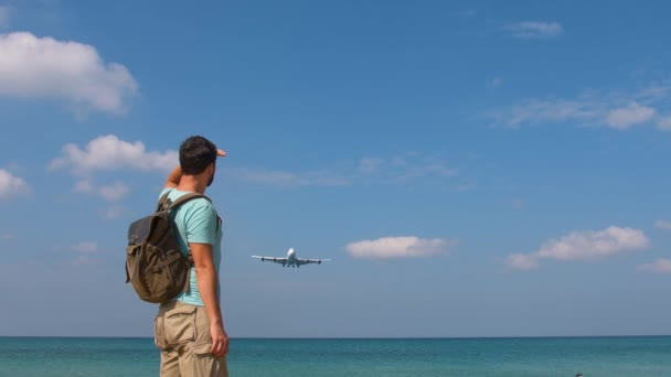 Tourist man with backpack welcomes airplane for travel. Hello vacation concept