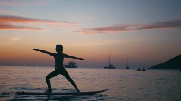 Mladá žena, která dělá jógu na desce sup s pádlem při západu slunce