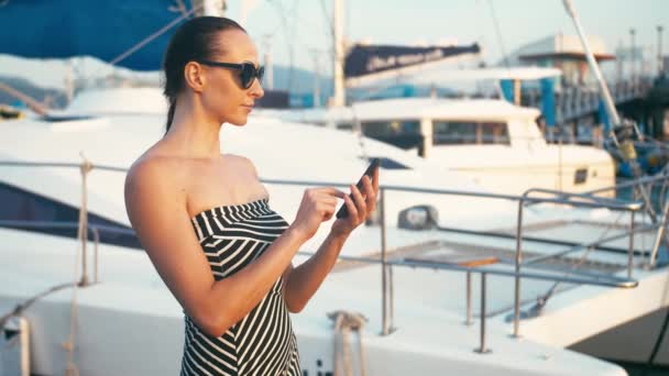 Classy lady in dress using her smartphone in marina pier with yachts at background