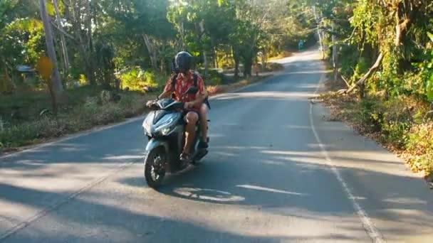 Mladé krásné turistické pár jede do džungle na skútr, helmy. Cestování, svoboda, štěstí, dovolenou, líbánky koncept.