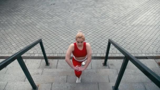 Plusz méretű vegyes verseny szőke mosolygós nő visel piros sportruházat bemelegítő futtatása előtt