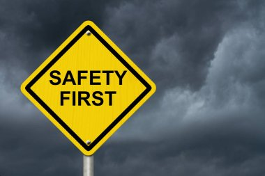 Safety First Warning Sign, Yellow warning sign with words Safety First Warning with stormy sky background