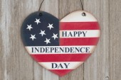 Photo Retro Happy Independence Day text on a heart shape wood sign with colors of the USA flag on weathered wood
