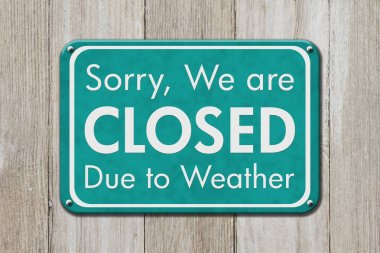 Closed due to weather sign, A teal sign with text Sorry we are closed due to weather on weathered wood