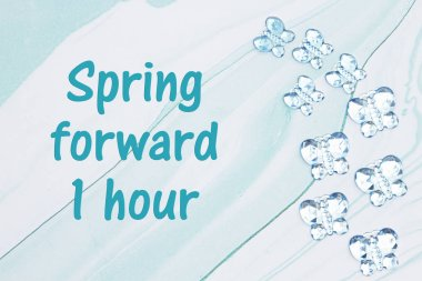 Spring forward 1 hour message with blue glass butterflies on blu