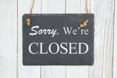 Sorry we're Closed text on a hanging chalkboard on weathered whi