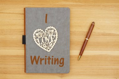 I love writing message with gray leather book with heart and pen