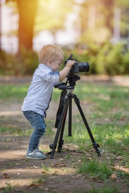 Two years old boy is photographer. Kid holds a camera on tripod and takes photo of landscape. Little child dressed shirt and jeans playing in the park.