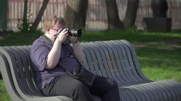 Junger Mann fotografiert im Park
