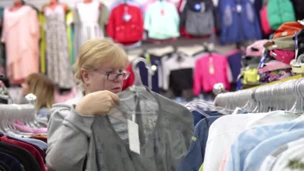 žena si vybírá oblečení v obchodě