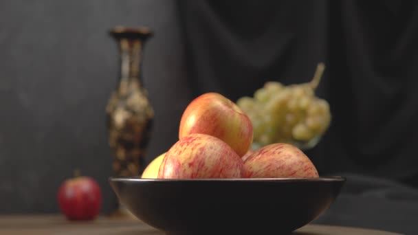 Still life with apples and grapes on a dark background