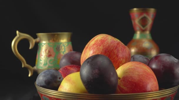 Still life with plums and apples on a dark background