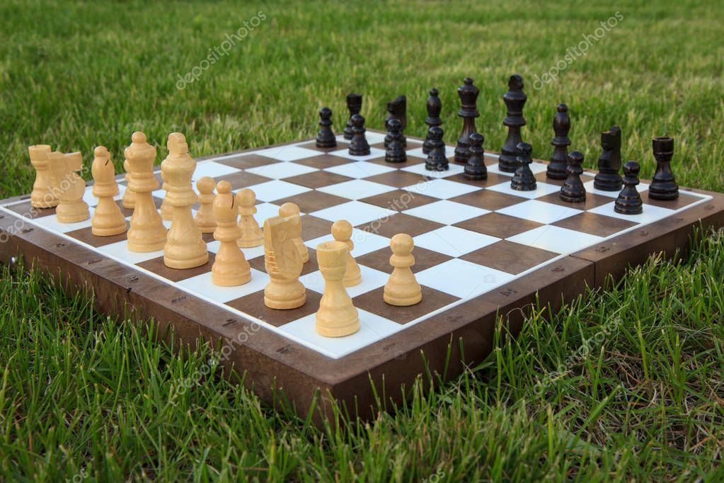 Chess board with chess pieces on green grass in daylight. Selective focus on white pieces. Outdoors chess game.