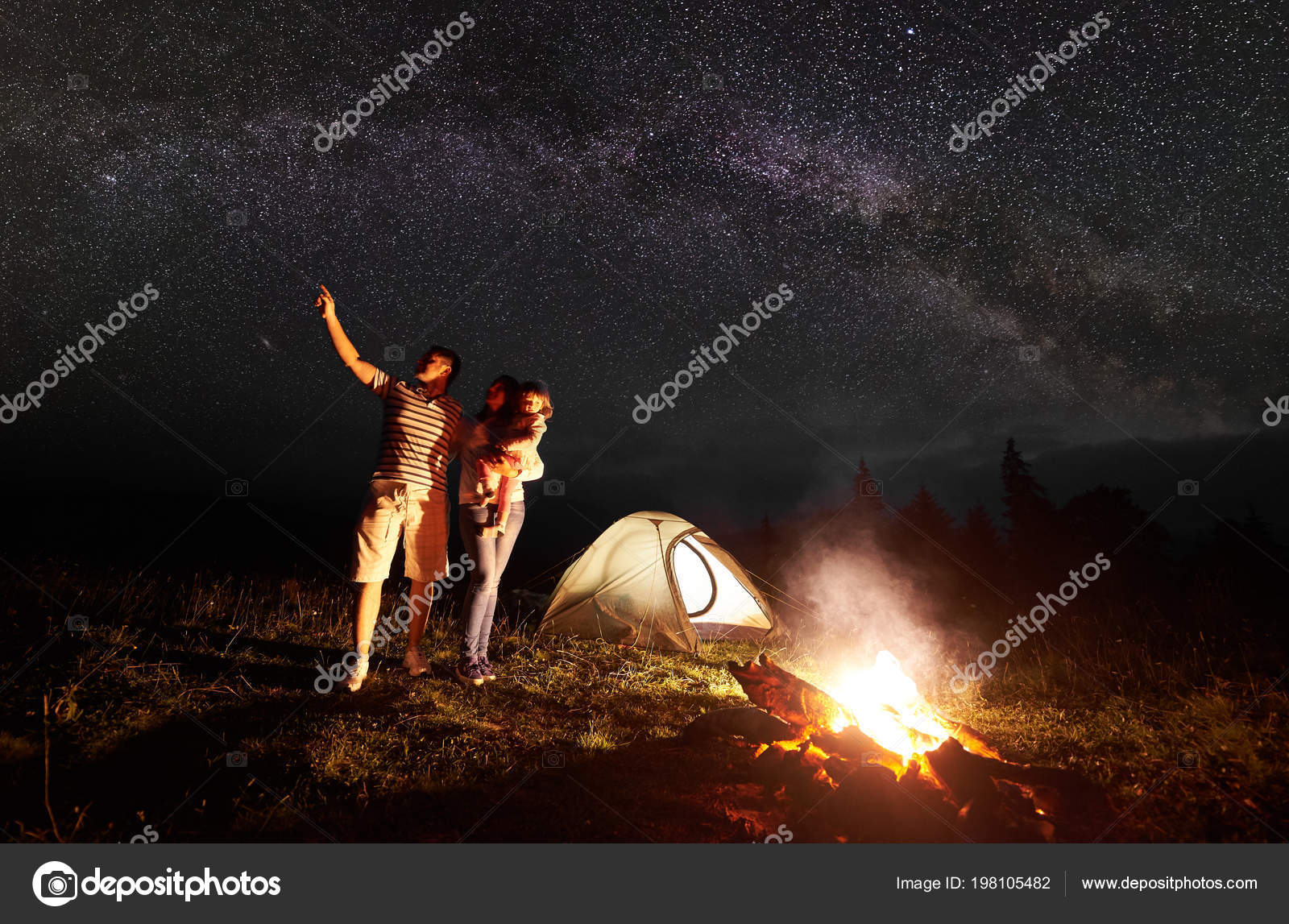 Tourist Family Camping In Mountains At Night Mother Holding Arms Small Daughter Father Pointing Bright Stars Dark Sky And Milky Way Front Of