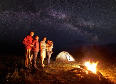 Night camping in mountains. People standing in front of burning campfire. Illuminated tent and starry sky and Milky way on background. Mother holding in arms daughter. Tourism and recreation concept.