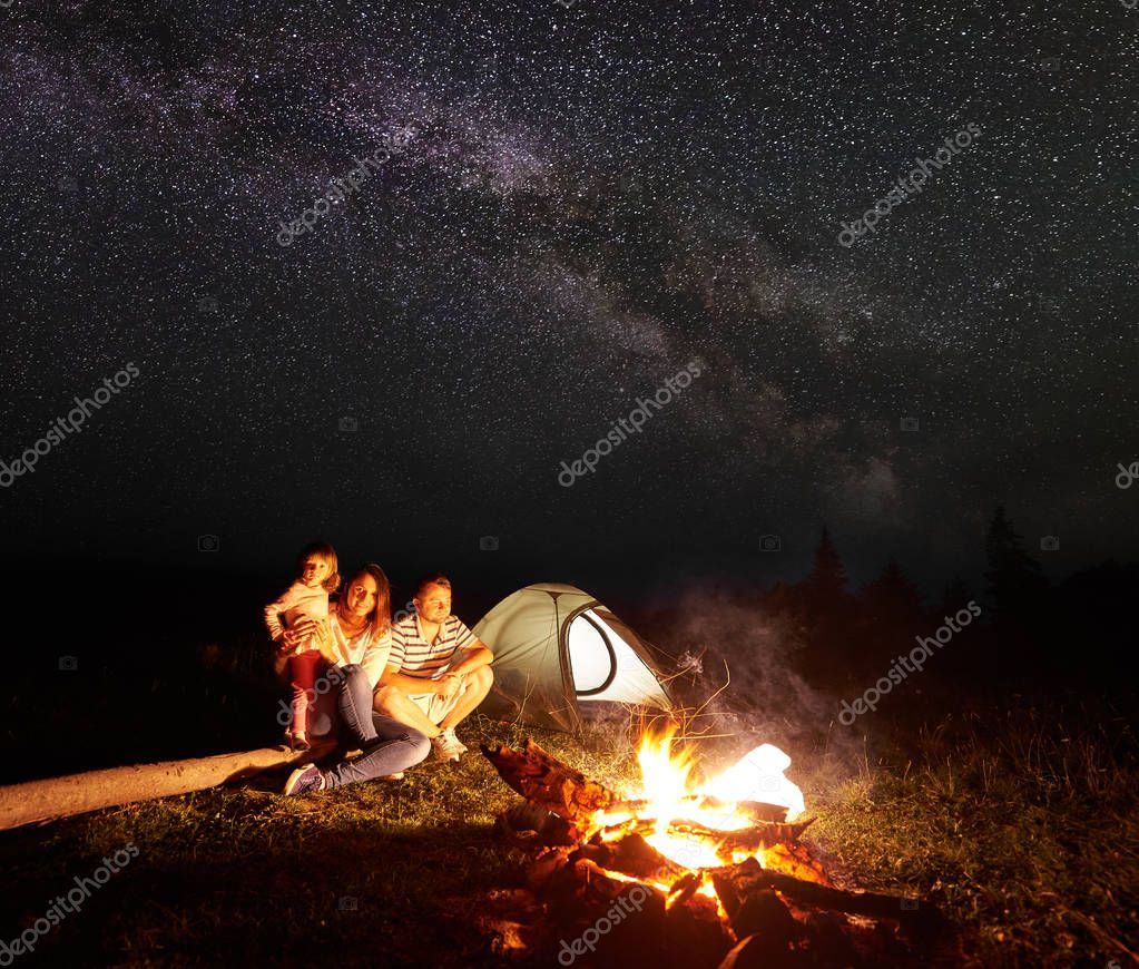 Family camping in mountains at night, sitting in front of illuminated tent and burning bonfire under bright stars in dark sky. Woman holds in arms small girl, smiling to the camera