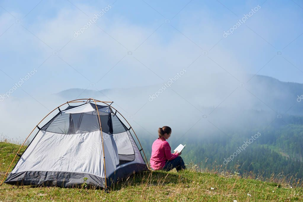 Back view of young long-haired tourist girl sitting on green grass of blooming valley at tourist tent under beautiful blue sky reading a book on bright summer morning on foggy mountains background.