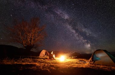 Camping in mountains. Young tourist man sits between two tents on grassy valley watching brightly burning campfire on beautiful dark blue starry sky background. Tourism and beauty of nature concept.