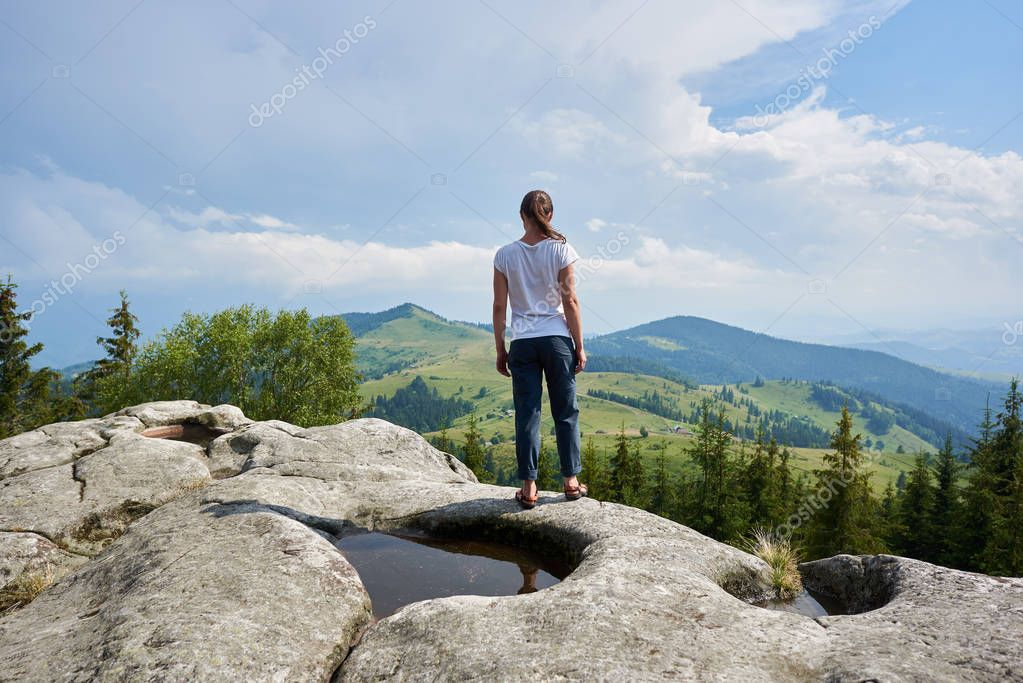 Back view of young tourist woman standing on huge rock with big puddle in the middle under beautiful blue sky enjoying fantastic view of mountains covered with ever-green pine forest. Carpathians