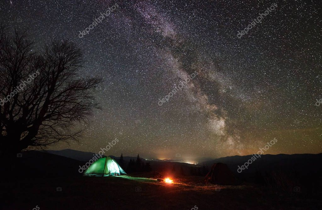 Bright bonfire burning near tourist illuminated tent. Night camping in mountain valley under beautiful sky full of stars and Milky way. Silhouette of big tree and distant hills in background