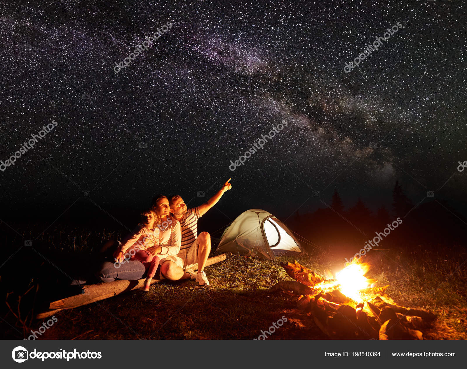 Tourist Family Camping In Mountains At Night Sitting On Log Near Illuminated Tent And Burning Bonfire Mother Holding Arms Small Daughter