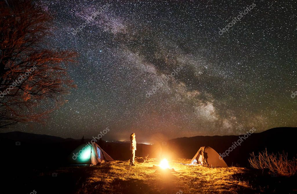 Peaceful camping night in mountains. Young tourist long-haired girl stands between two tents at burning campfire watching deep dark sky with lot of bright sparkling stars. Tourism and travel concept.
