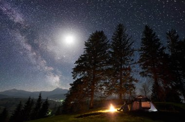 Male tourist sitting alone in front of tent at burning bonfire on grassy valley enjoying night blue starry sky with Milky way and bright full moon. Pine trees forest on background. Mountain camping