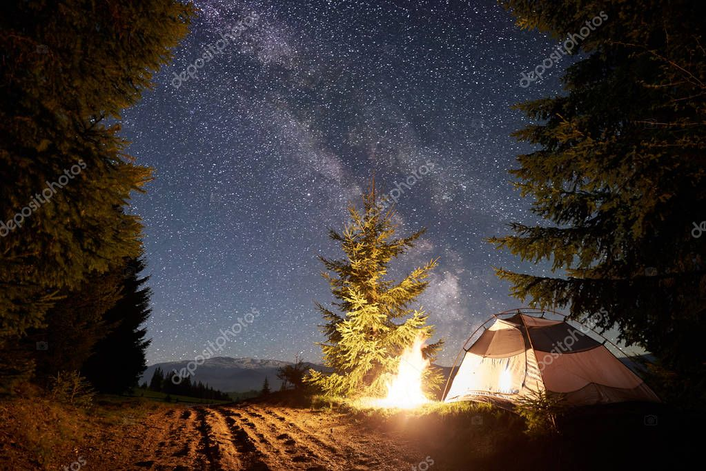 Night camping in mountains. Tourist tent by brightly burning bonfire near forest under clear dark blue starry sky, Milky way. High pine trees on background. Beauty of nature and tourism concept.