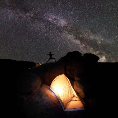 Camping at night on rock formation. Brightly lit tourist tent and small silhouette of woman doing gymnastic yoga exercises on mountain top against starry sky. Active lifestyle concept. Virabhadrasana