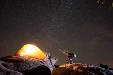 Attractive girl doing bending gymnastic yoga exercises on big boulder on starry night sky, brightly lit tourist tent and black mountains background. Tourism, hiking, active lifestyle, camping concept.