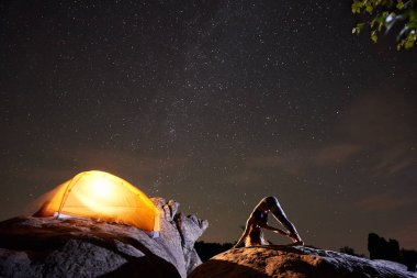 Attractive athletic girl doing complicated gymnastic exercises on big boulder on starry sky and brightly lit tourist tent background. Tourism, hiking, active lifestyle, mountain night camping concept.