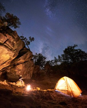 Campsite night amid huge steep rock formations. Attractive woman sitting on boulder watching bonfire in front of tourist tent on blue starry sky background. Tourism, sport and camping concept.