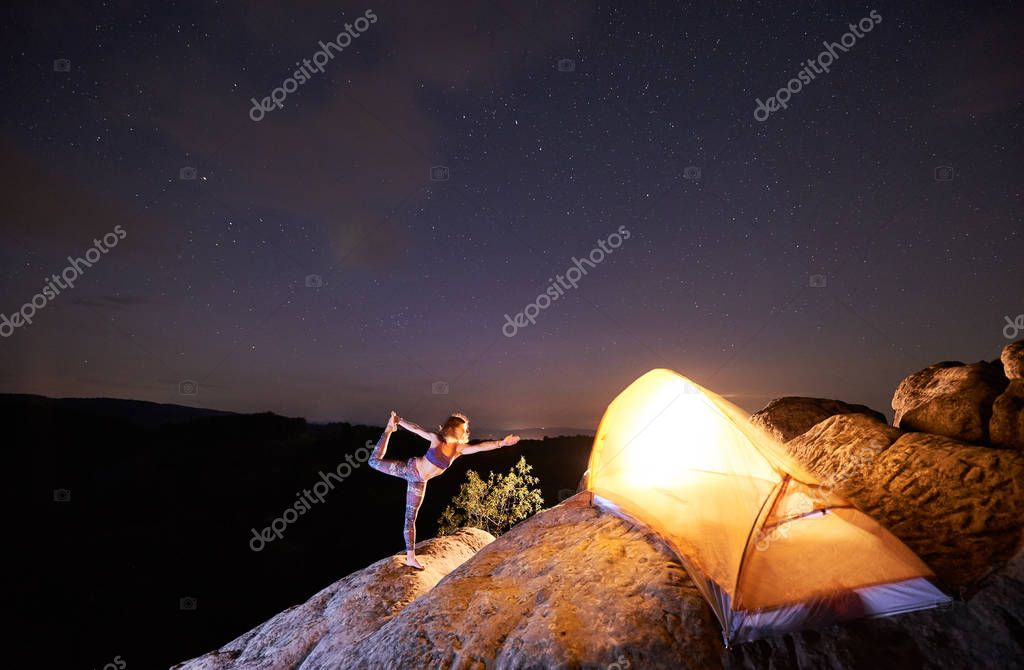 Woman in complicated yoga pose standing on one leg on steep rock in front of tourist tent on starry evening sky and black mountains background. Tourism, active lifestyle, camping concept. Narajasana