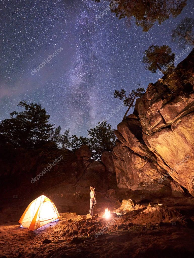 Campsite at night amid huge rock formations. Athletic slim barefooted girl standing straight between small tourist tent and burning bonfire under clear dark starry sky. Tourism and camping concept.